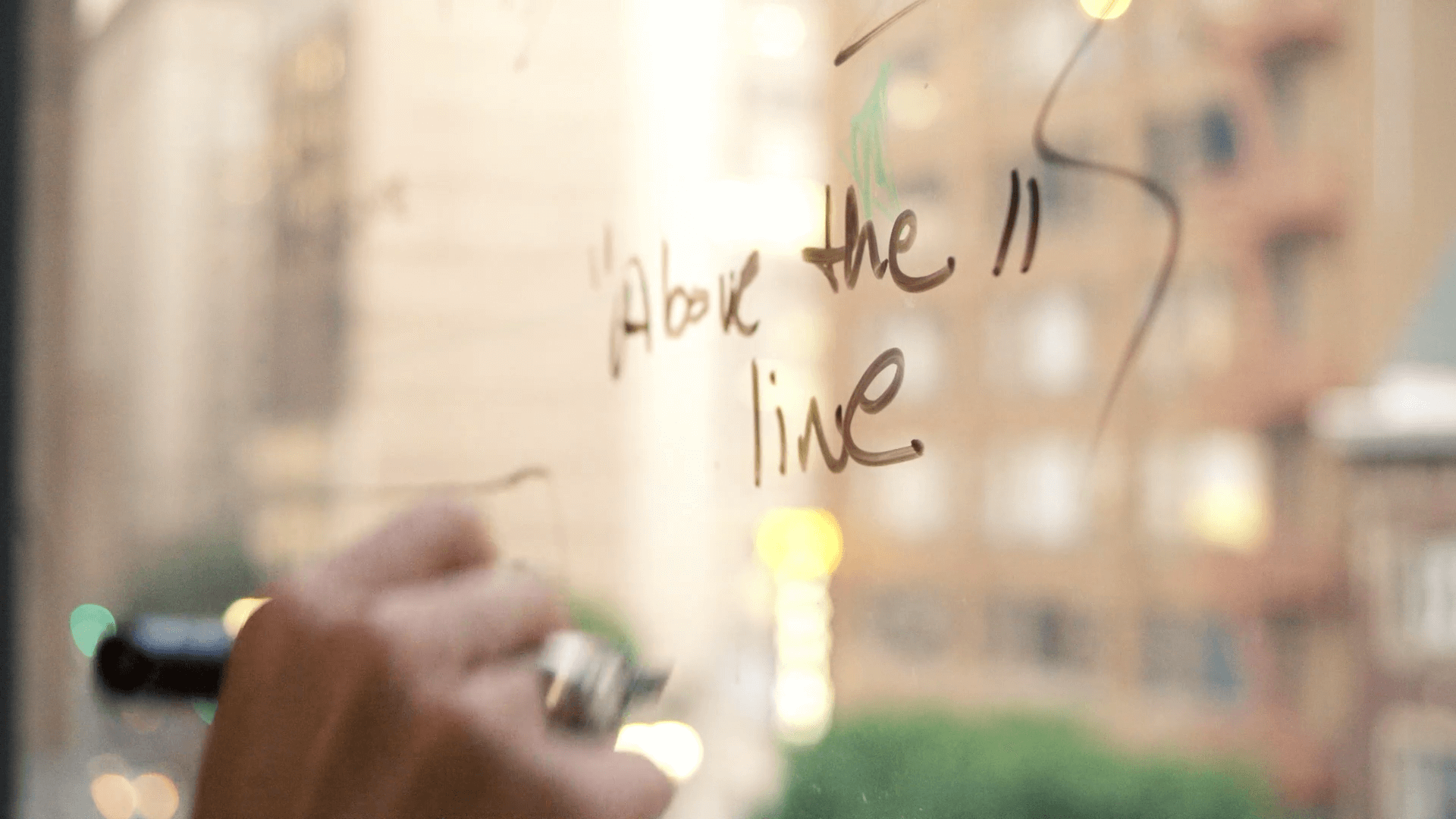 person writing with marker on a window, reads